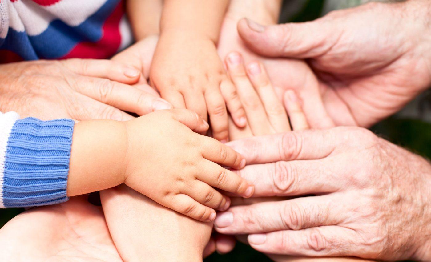 Übereinander liegende Händer von Menschen allen Alters.